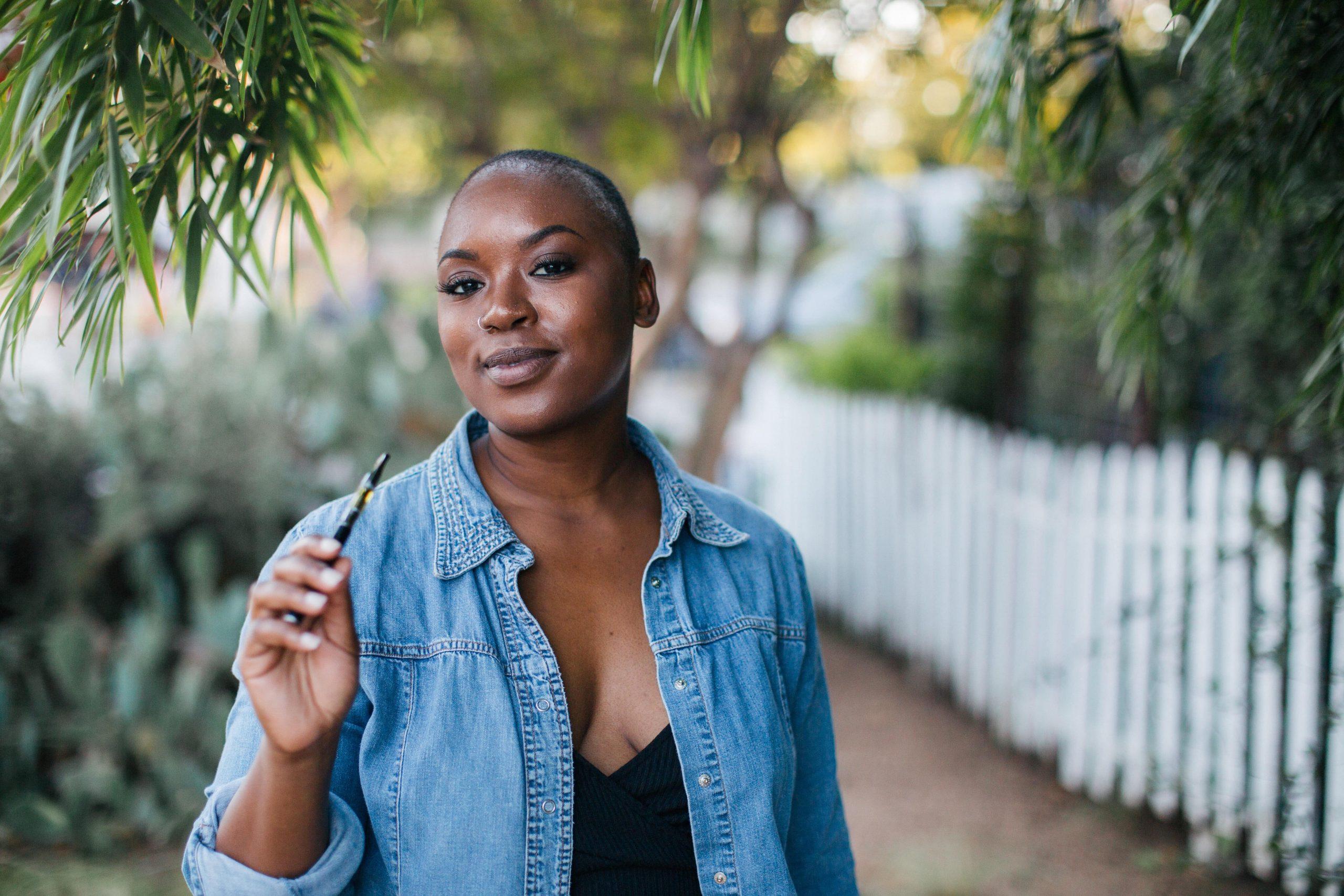 femme avec une cigarette électronique dehors